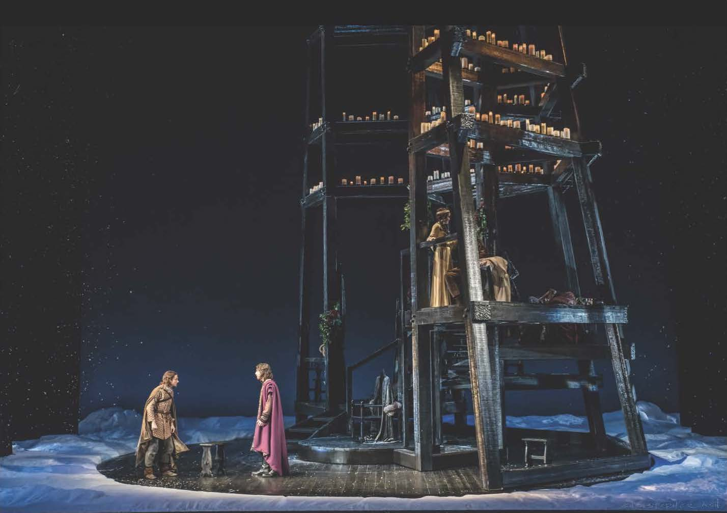 two people standing next to a large wooden structure on a circular wooden platform on a dark stage