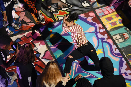 Ruby Morales dancing in a group with colorful background