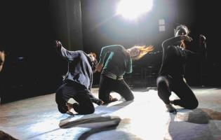 three dancers kneeling and leaning to the right with a bright light above them
