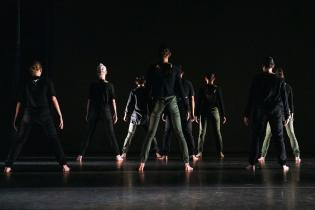 A group of dancers with their backs facing the camera and wearing black with a black background